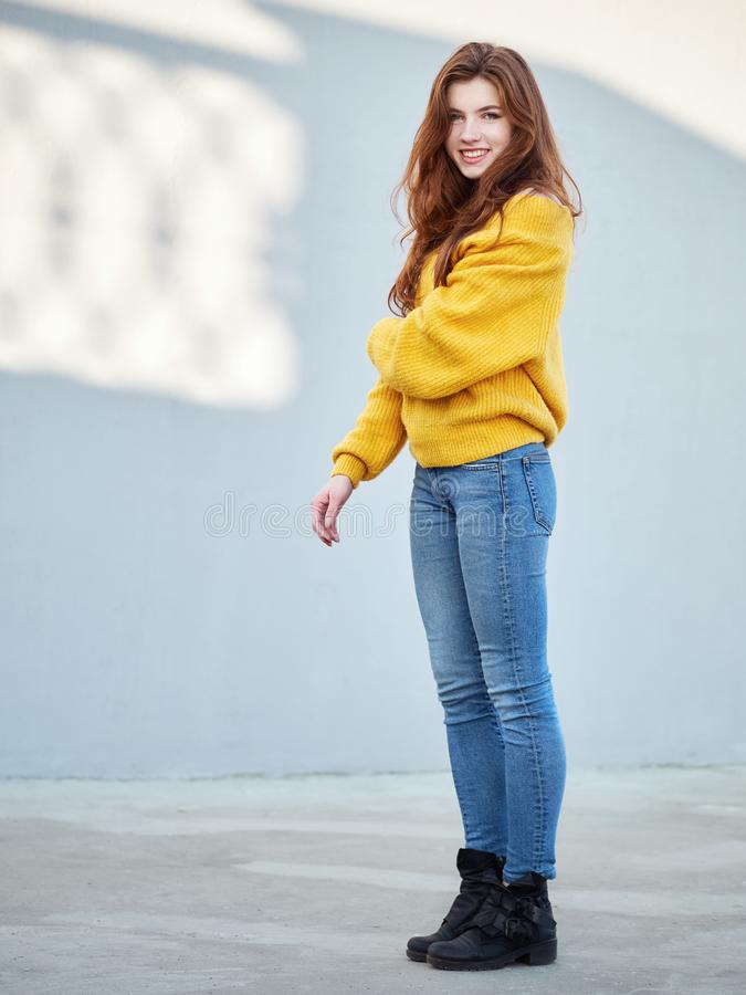 美妙的红头发人妇女充分的身体射击有长发的在获得黄色的毛线衣在灰色混凝土墙背景的乐趣与太阳 图库摄影