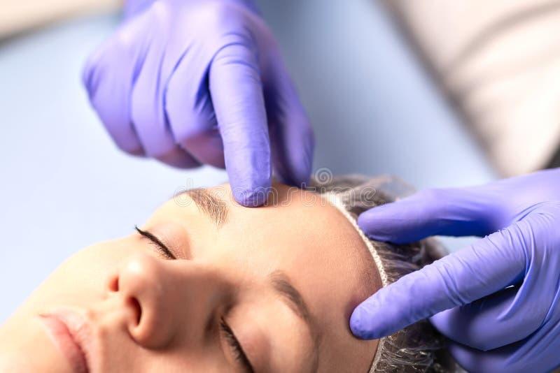 美容师、整形外科医生或者医生有患者或顾客的 咨询和计划在面部手术前在医院 免版税库存图片