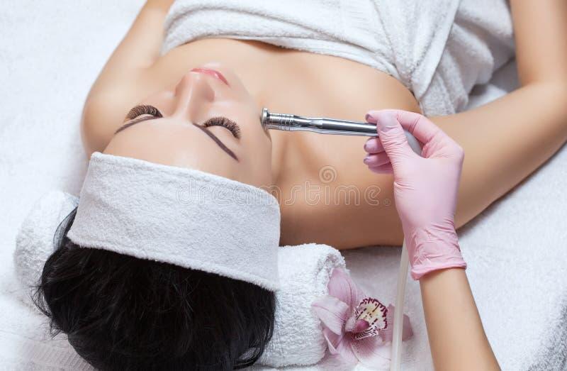 美容师做做法Microdermabrasion一个美丽,少妇的面部皮肤 库存照片