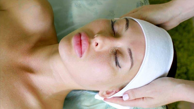 美容师在年轻女人上把头饰带放在治疗前在温泉沙龙 图库摄影
