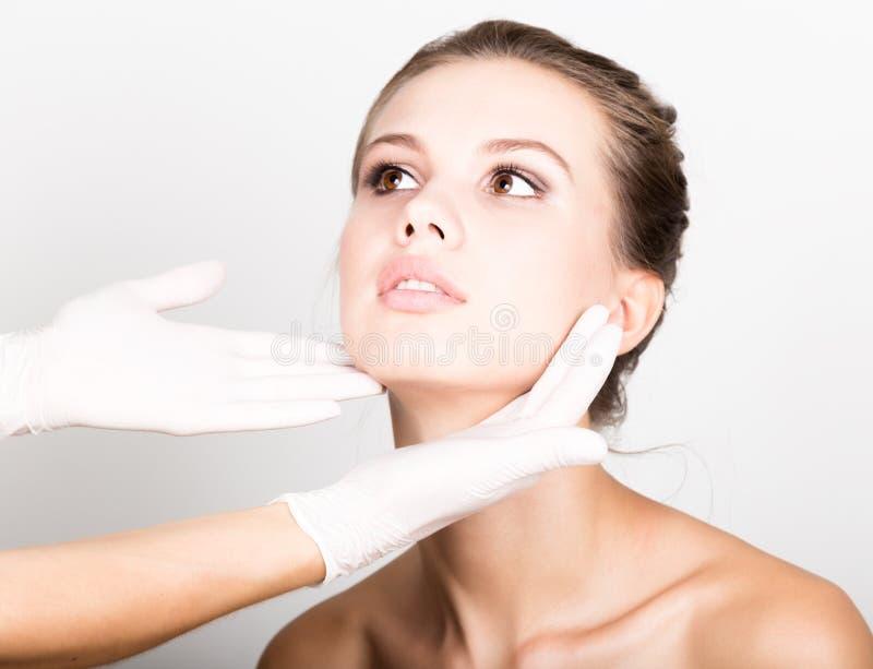 美容师审查美丽的年轻女性面孔的手` s 免版税库存照片