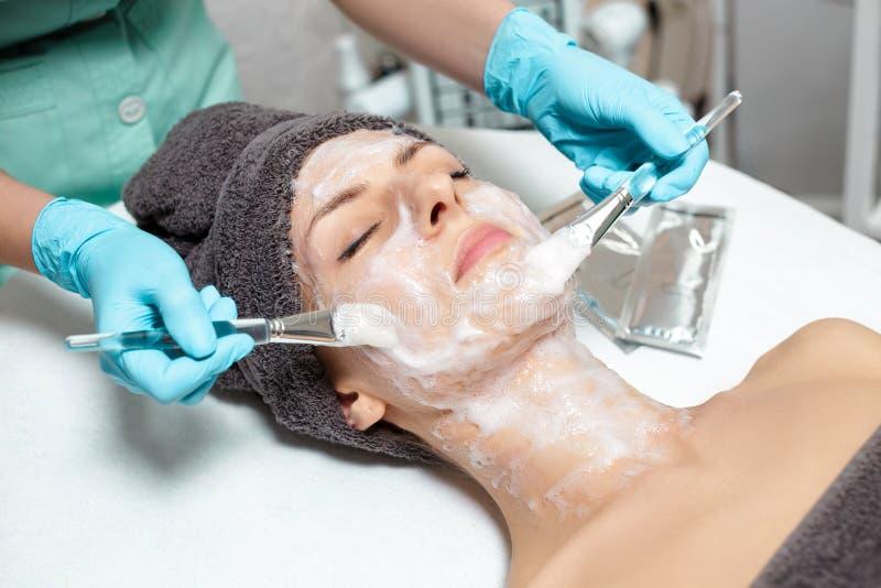 美容师应用在美丽的少妇的面罩温泉沙龙的 化妆做法护肤 Microdermabrasion 库存图片