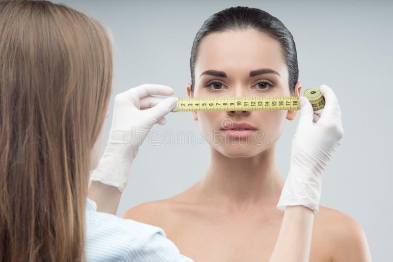 美容师手被测量的妇女头 库存图片