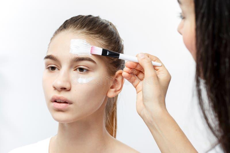 美容师申请与在年轻棕色毛发的女孩的面孔的一个刷子白色化妆面具 免版税库存图片