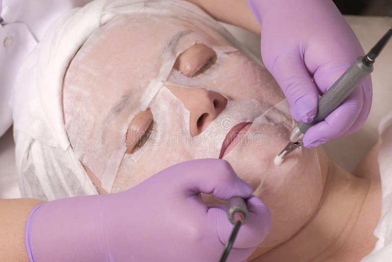 化妆做法 美容师的手淡紫色手套的拿着在妇女的下巴的电极 Microcurrent脸面护理 免版税库存图片