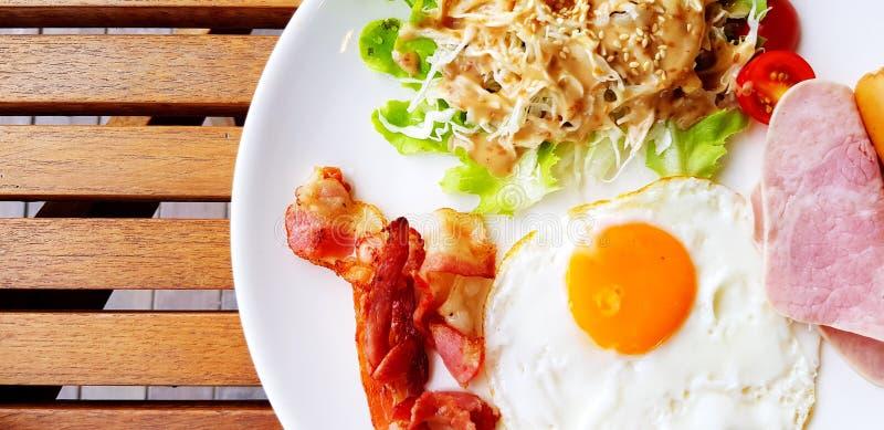 美式或英式早餐,包括炸鸡蛋、培根猪肉、沙拉酱或在木桌上白盘的蔬菜上调味 免版税库存图片