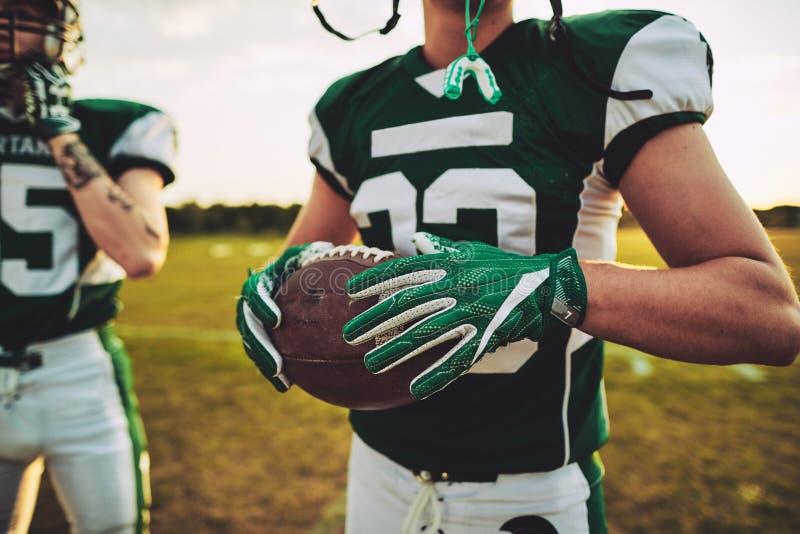 美式足球与一个队友的四分卫身分在PR期间 免版税库存照片