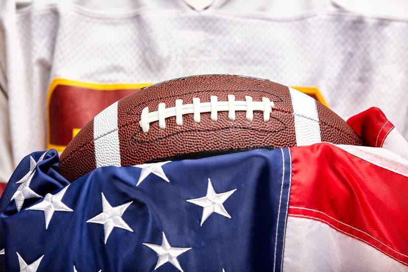 美式足球概念、球在美国国旗背景和美式足球制服 免版税图库摄影