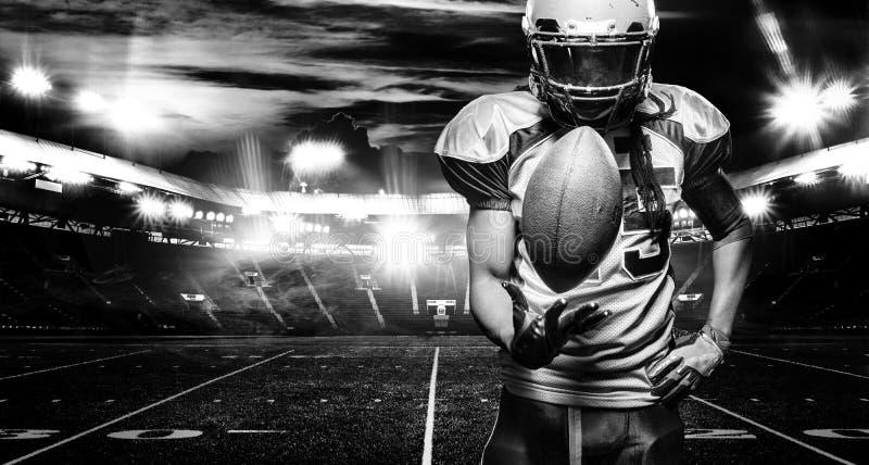美式足球球员,盔甲的运动员与在体育场的球 北京,中国黑白照片 与copyspace的体育墙纸 免版税图库摄影
