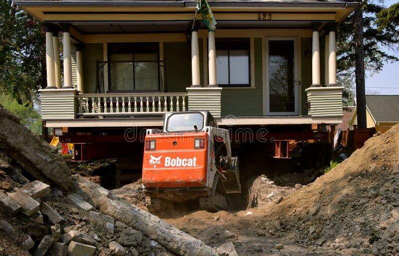 美洲野猫挖掘机从下面移动地球被顶起房子 免版税库存照片