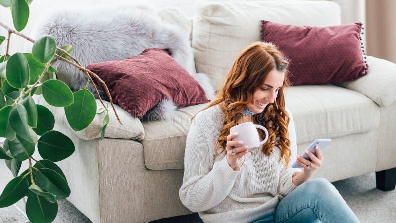 妇女休闲舒适家庭杯子浏览智能手机 免版税库存照片