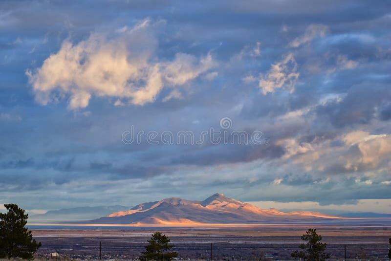 羚羊从优秀大学毕业生,在日出的清扫的cloudscape的海岛视图与大盐湖国家公园在冬天 美国犹他 免版税库存照片