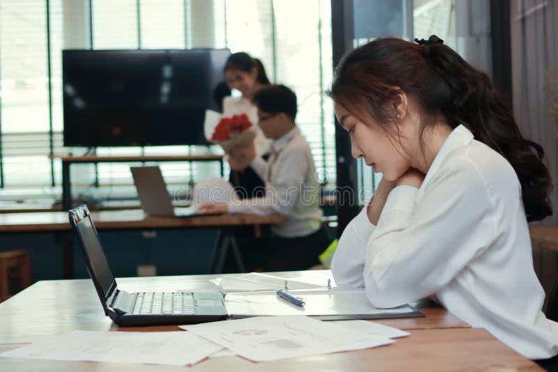 羡慕恼怒的年轻亚裔女商人与在爱的富感情的夫妇一起使用在办公室背景中 嫉妒和妒嫉frien 免版税库存照片