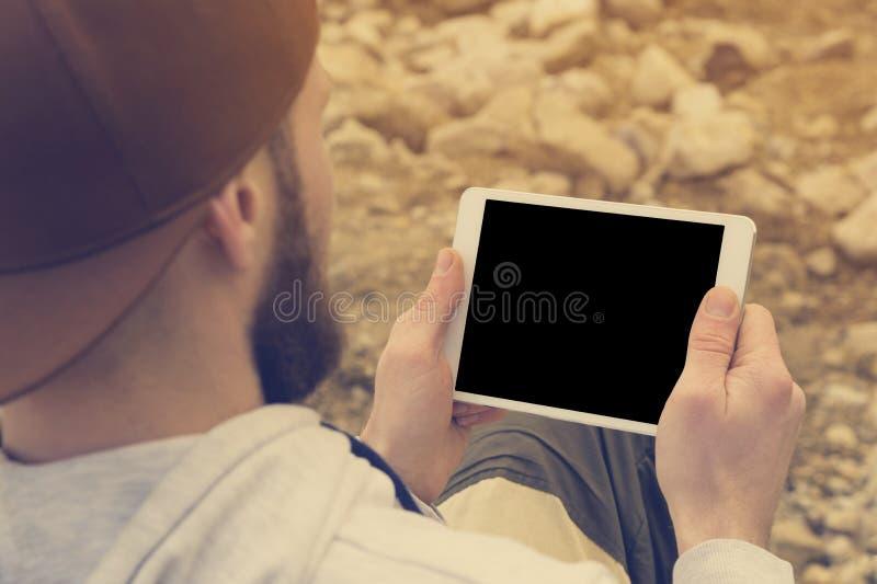 群众的特写镜头在一个棕色盖帽的在他的手上露天拿着一台白色片剂个人计算机 一个有胡子的人看 库存照片