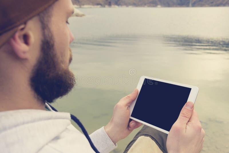 群众的特写镜头在一个棕色盖帽的在他的手上露天拿着一台白色片剂个人计算机 一个有胡子的人看 图库摄影