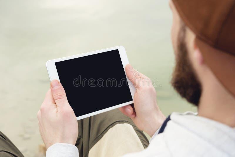 群众的特写镜头在一个棕色盖帽的在他的手上露天拿着一台白色片剂个人计算机 一个有胡子的人看 库存图片
