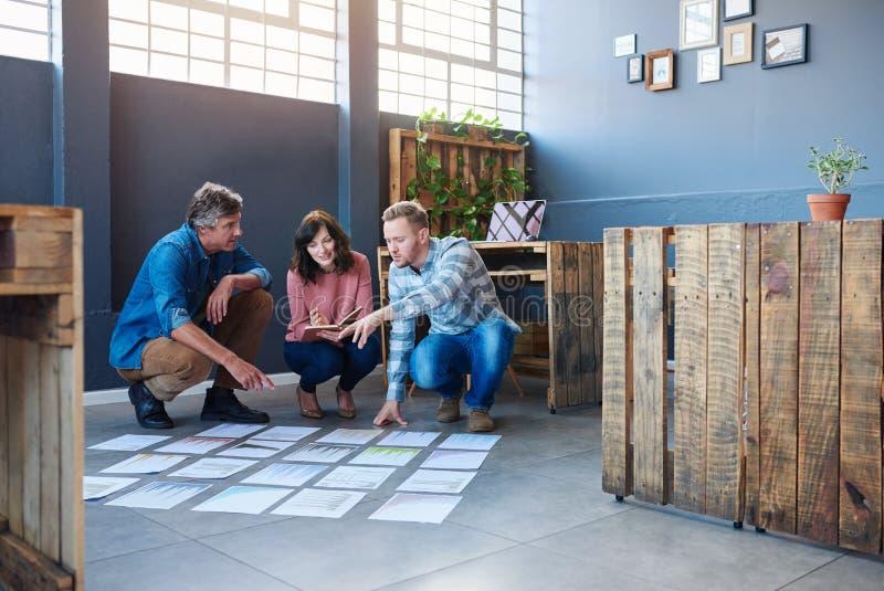 群策群力与在一个现代办公室地板上的纸的被聚焦的工友 图库摄影