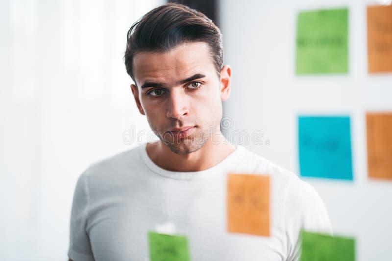 群策群力经营战略身分的商人在玻璃墙后的办公室空间有稠粘的笔记的 免版税库存照片