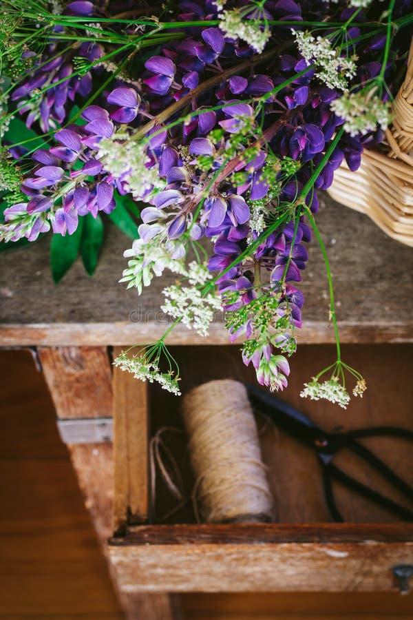 羽扇豆和野胡萝卜花束在葡萄酒桌,黑暗和喜怒无常的样式 免版税库存照片