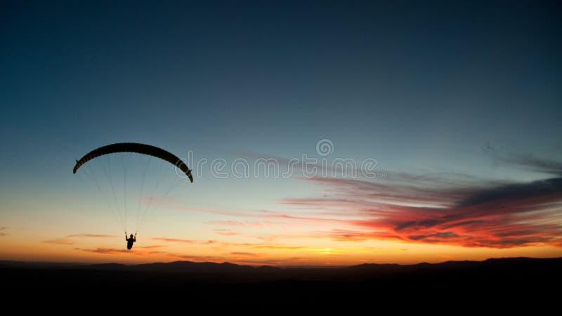 滑翔伞剪影在日落的 库存照片