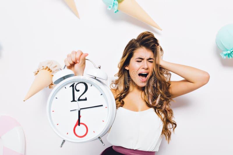 翻倒与眼睛的女孩尖叫结束了接触在恐慌的头和拿着大白色时钟 困厄的年轻人画象  库存图片