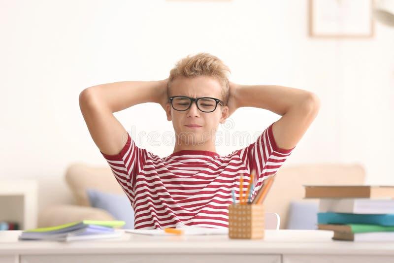 翻倒在家做家庭作业的少年男孩 库存图片