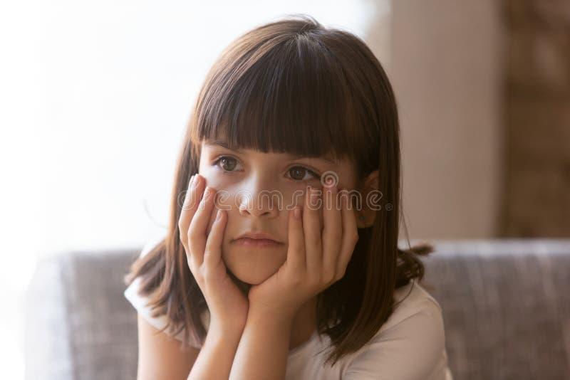翻倒女孩坐长沙发在家感觉不快乐 库存图片