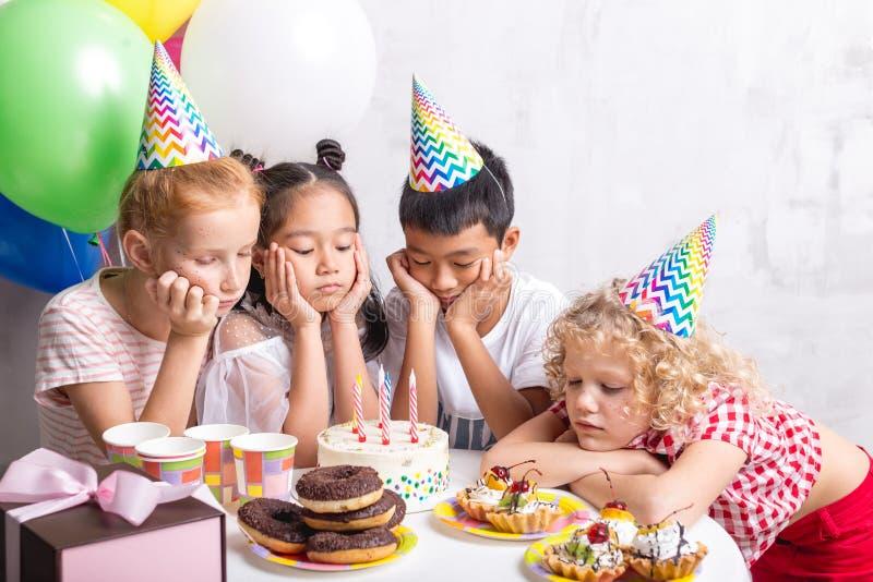 翻倒孩子在桌和看鲜美蛋糕附近聚集了 免版税图库摄影