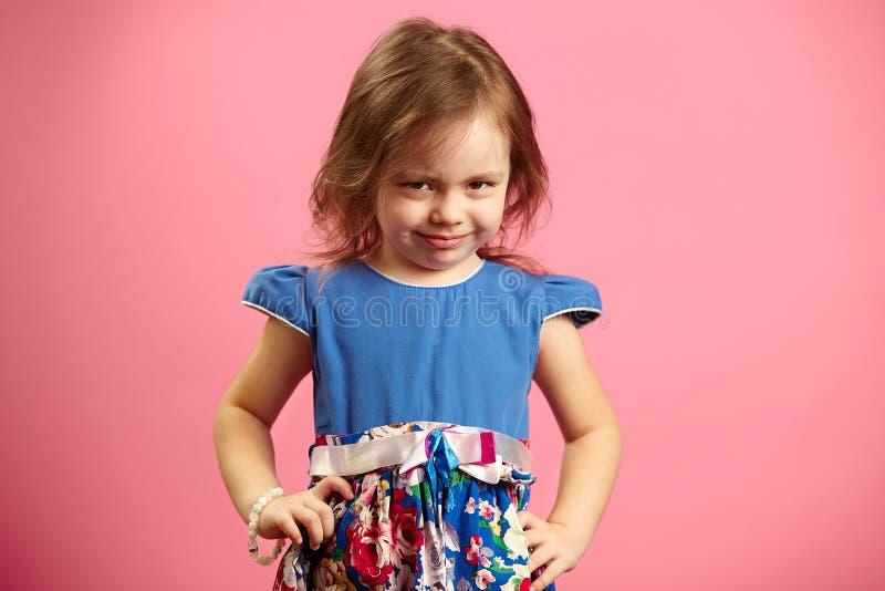 翻倒小女孩画象在桃红色被隔绝的背景的三年,表示失望或怨气,展示 库存图片