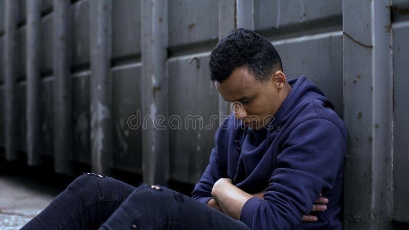 翻倒少年坐在门户的,面对生活困难,无家可归者的移出境者 库存图片