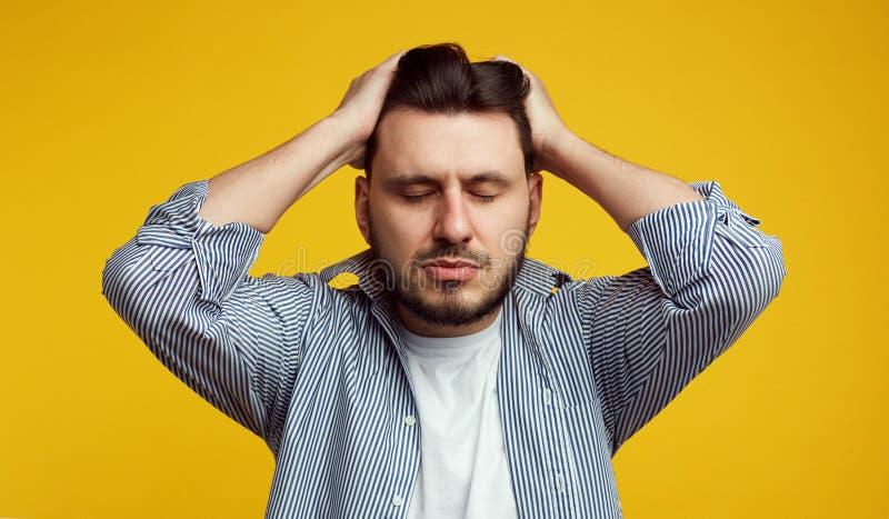 翻倒年轻人保留在头的两只手,闭上眼睛,遭受偏头痛,有表情佩带的哀伤的疲劳 库存照片