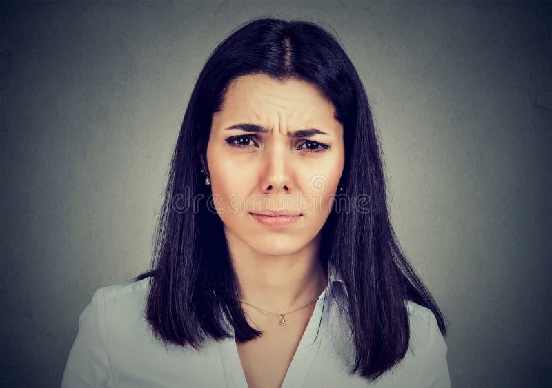 翻倒注重了有严肃的妇女皱眉的头疼看照相机 库存图片