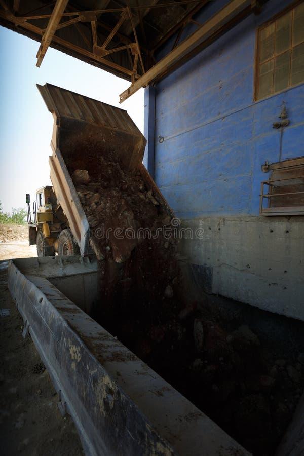 翻斗车、倾销者或者翻斗卡车在沙子猎物卸载石头,运输材料在自然本底 免版税库存照片