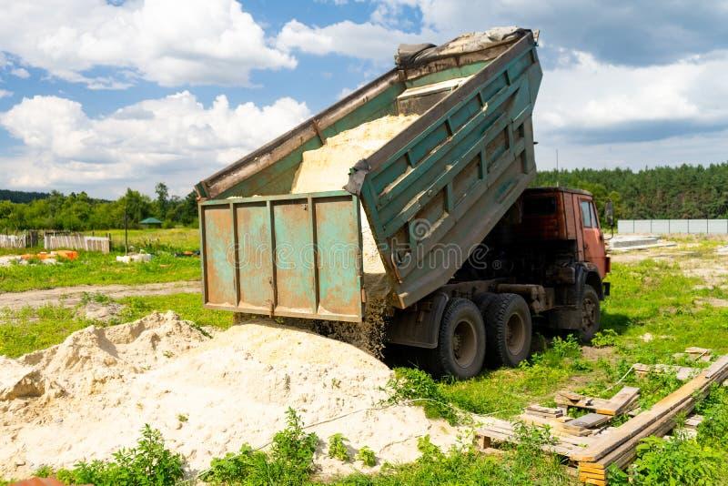 翻斗车卸载沙子 卡车倾销了货物 沙子和石渣 建造场所,材料仓库 免版税库存照片