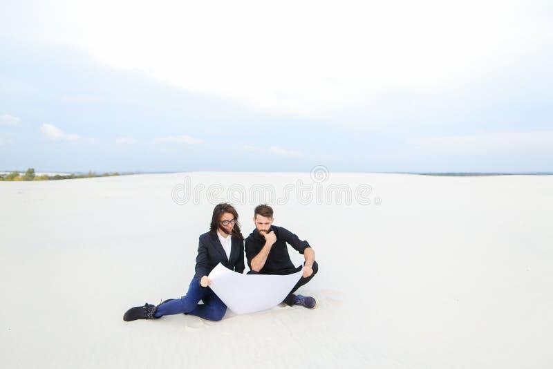 翻译妻子和丈夫计划房子在海边 库存照片