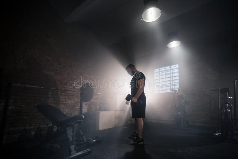 翻转单手哑铃的举重运动员 免版税图库摄影