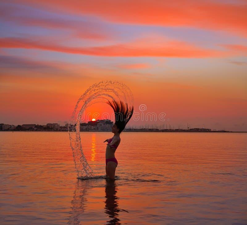 翻转头发轻碰的女孩在日落海滩 库存照片