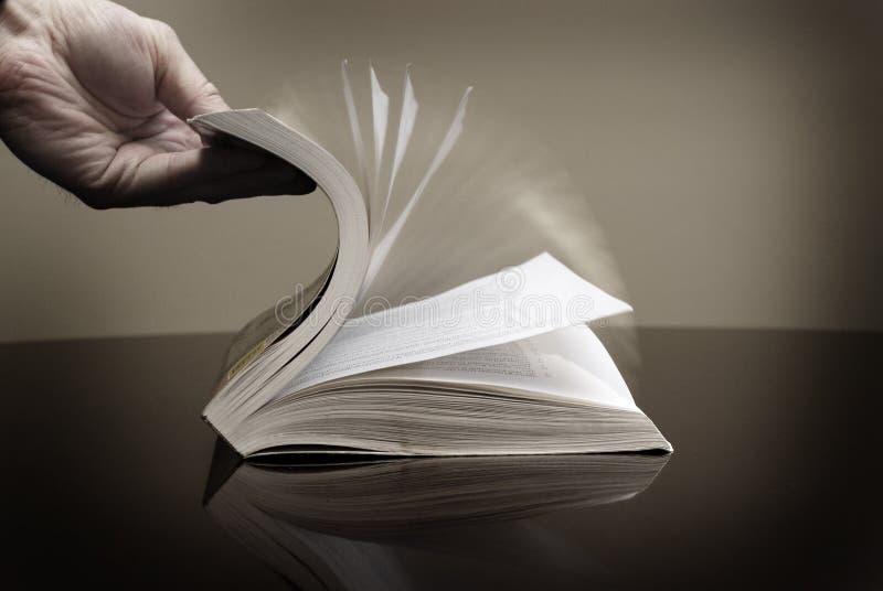 翻转页信息读书的书和手 免版税库存照片