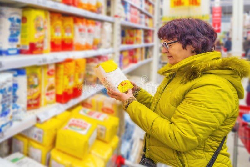 翼果2019年3月:美丽的成熟妇女在超级市场选择面粉 库存照片