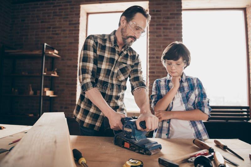 老两个好人被集中的被聚焦的木工主要工匠杂物工爸爸爸爸教的儿子画象  免版税图库摄影