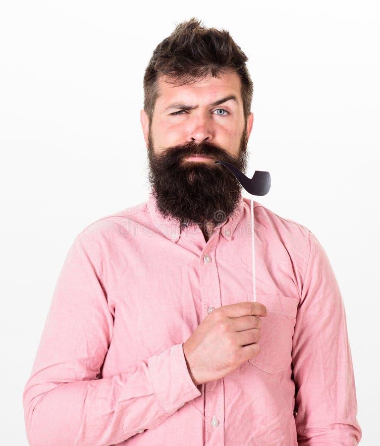 老习性概念 供以人员拿着纸党支柱烟斗,白色背景 有胡子和髭的行家 库存照片