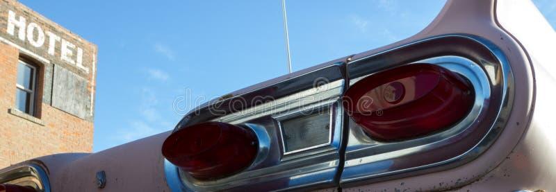 老五十年代汽车在一家老被放弃的旅馆外面, 免版税库存图片