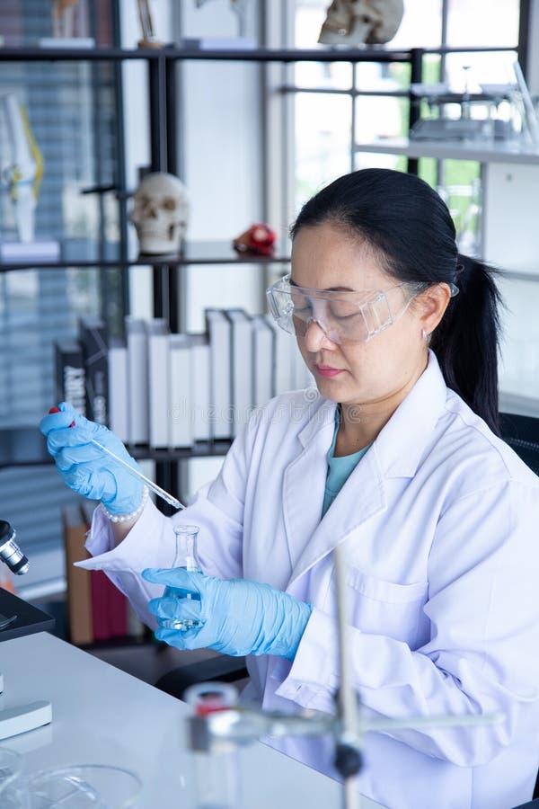 老亚洲妇女科学家下落溶解的化学制品到烧瓶里 库存图片