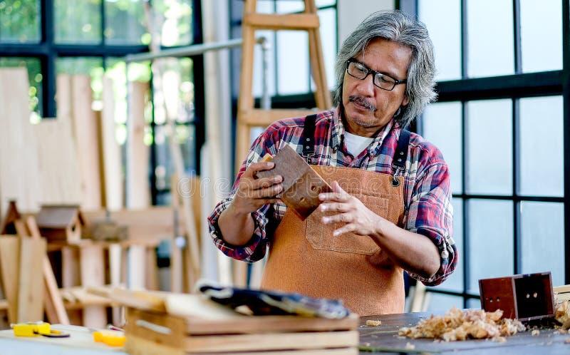 老亚洲工匠举行木小屋和看到它,在有木堆的与玻璃的屋子和周围里 库存照片