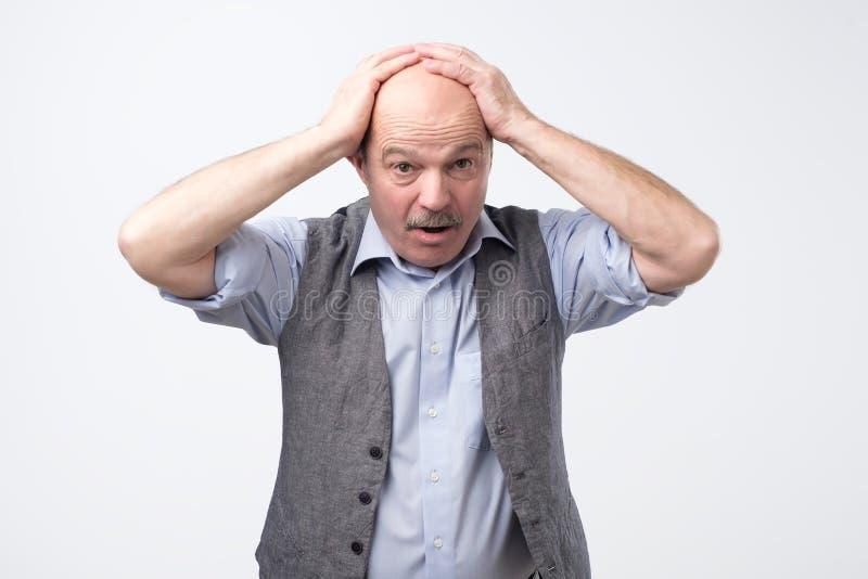 老人不可能控制恐慌和注重在顶头开放嘴的藏品手 图库摄影