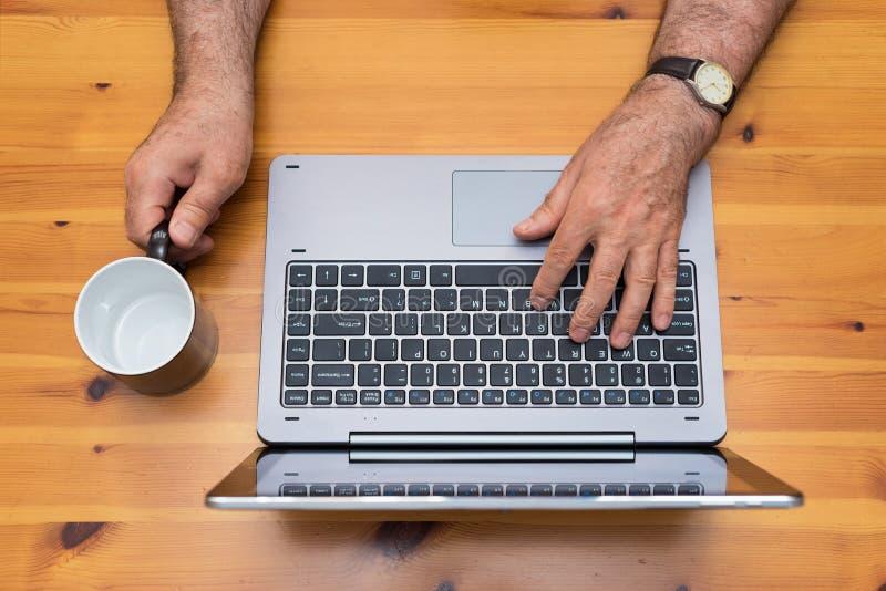 老人与膝上型计算机一起使用 空的杯子, cofee断裂时间 免版税库存图片