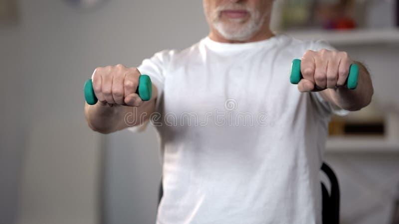 老人举的哑铃、训练肌肉和联接在伤害或侮辱以后 免版税库存图片