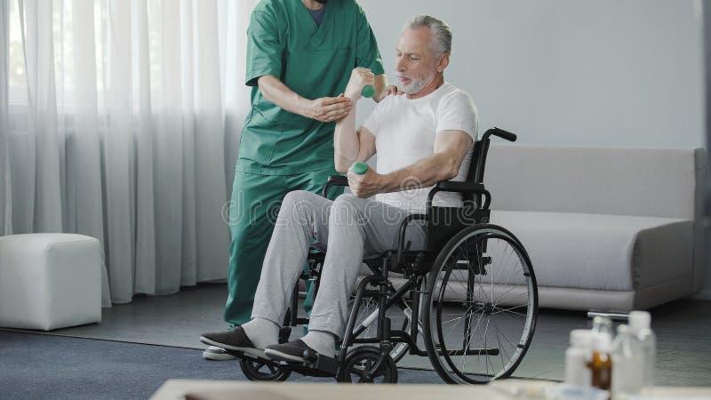 老人举的哑铃,坐在轮椅在康复中心 免版税库存照片