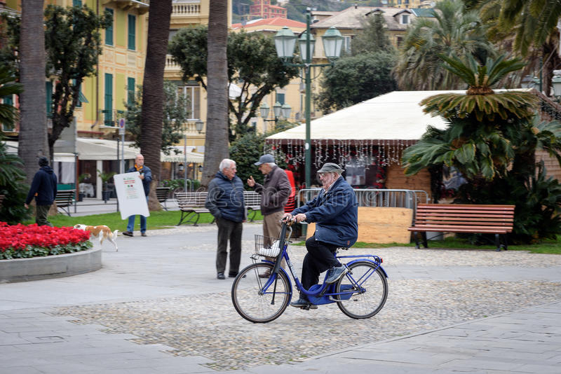 老人乘在圣诞老人Margherita镇,利古里亚,意大利街道上的自行车驾驶  库存照片