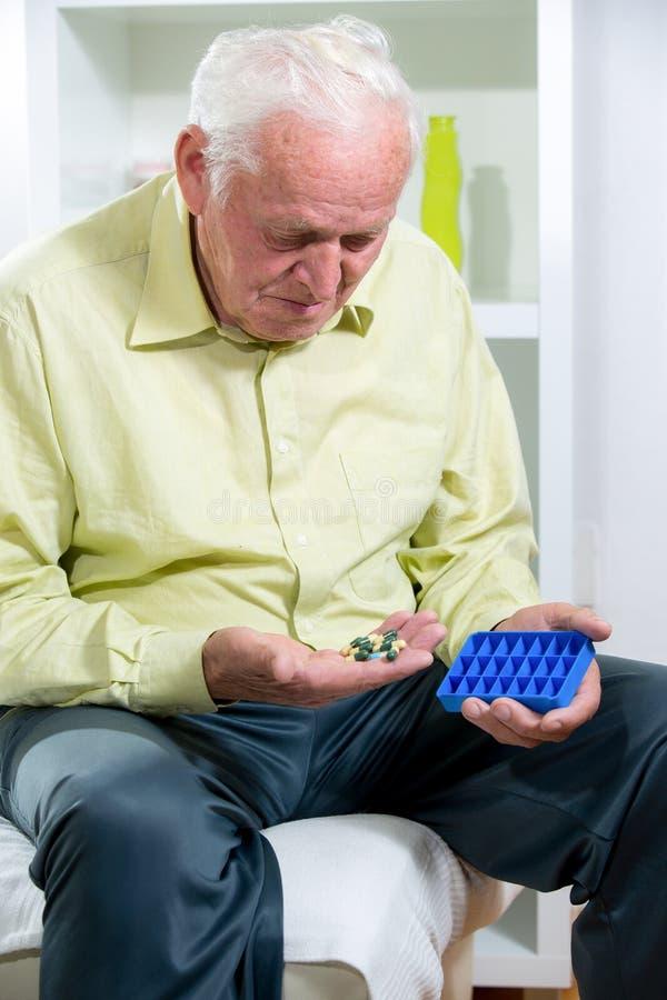 老人使用一个药片组织者 免版税库存照片